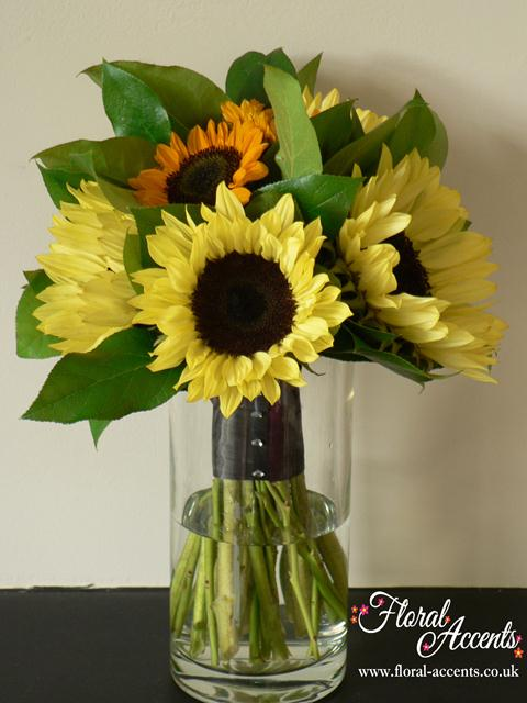 Vase filled with bright yellow sunflowers and mini yolk-yellow sunflowers and salal foliage