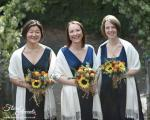 Bridemaid bouquets of large yellow sunflowers, orange carthamus, deep red spray roses and eucalyptus